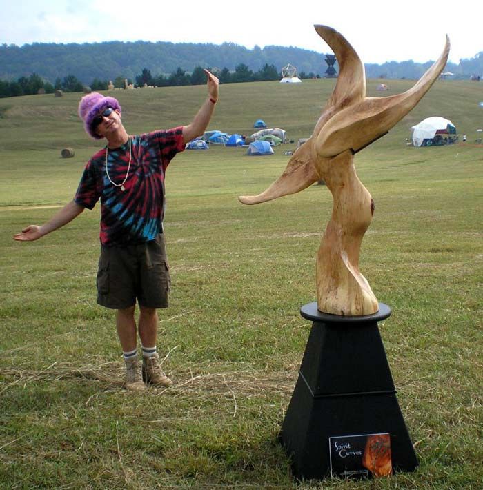 Sculpture - The Crossover, with Artist Gregor posing in a grassy, open field