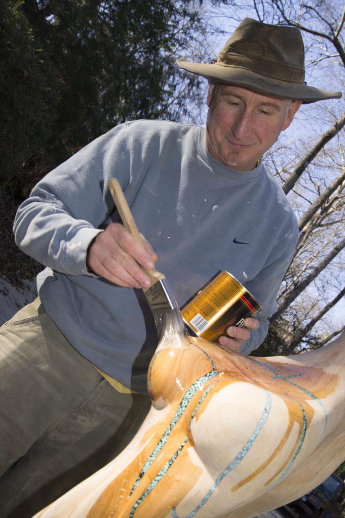 Gregor paints finish on sculpture